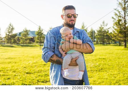 Happy father holding baby son, throwing baby in air. Concept of happy family, father's day and child