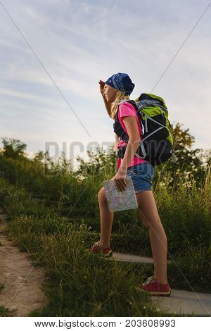 Teenager traveler with backpacks climbs the mountain. Wanderlust travel concept.