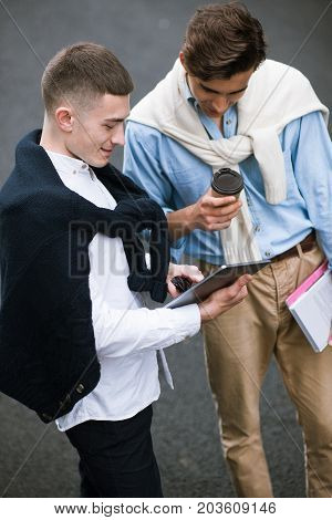 Modern young men on coffee break. Street style. Interesting leisure time for students, stylish youth, technology concept
