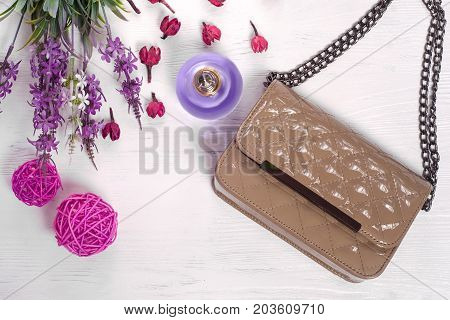 Flowers perfume handbag on a white wooden background