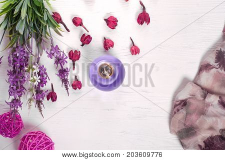 Flowers perfume shawl on white wooden background