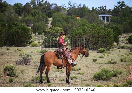 Cowboy Riding Horse In Desert With A Gun In His Hand. Concept Train Robbery.