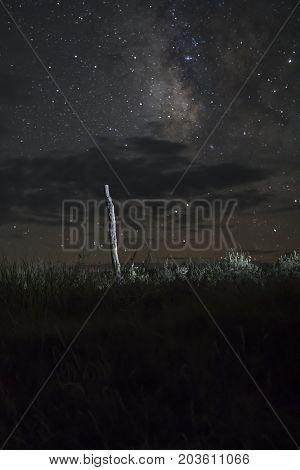 Milky Way in night skies over fence post in rural field.