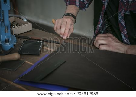 Workflow on table. Leather manufacturer working with tool on wooden table with prepared template of leather. Production of various type of leather product in workshop