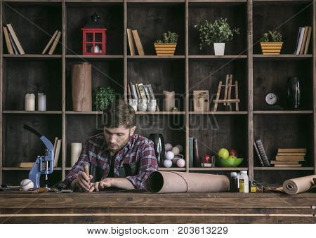 Neat work with tool. Young man leather manufacturer sitting at wooden table and using awl to make cutting leather in creative home studio. Small handmade business