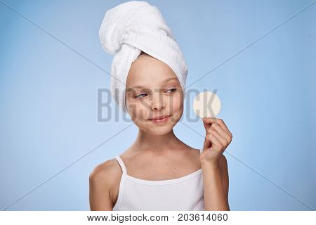 little girl with a towel on her head holds a cotton ball.