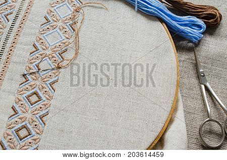 Embroidery design by brown and beige cotton threads on flax. Design of ethnic ornament. Background with embroidery texture.
