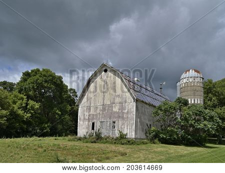 Weathered Barn And Silo Under A Cloudy Sky