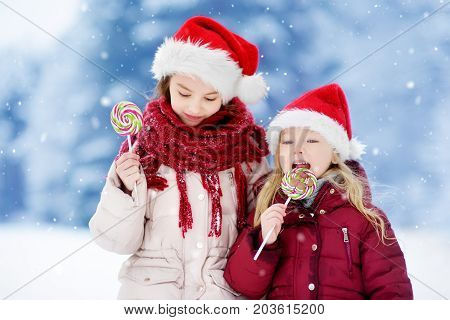 Two Adorable Little Sisters Wearing Santa Hats Having Huge Striped Christmas Lollipops On Beautiful