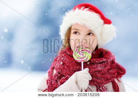 Adorable Little Girl Wearing Santa Hat Having Huge Striped Christmas Lollipop On Beautiful Winter Da