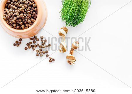 pet care with dry food for pet - dog in plastic bowl on white desk background top view space for text