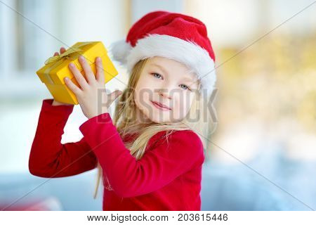 Adorable Little Girl Wearing Santa Hat Opening A Giftbox On Christmas Morning
