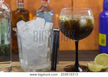 Pouring cola  into glass  to make a cuba libre cocktail