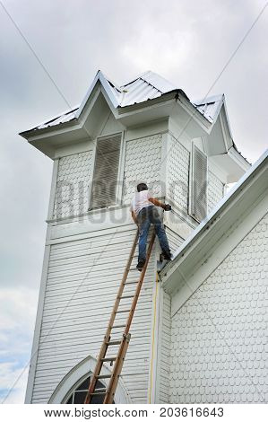Young man balances on a ladder leaning against a church in Northern Arkansas. He is in the process of helping to reroof an old church.