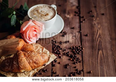 Coffee cup of cappuccino and coffee beans on brown wooden table