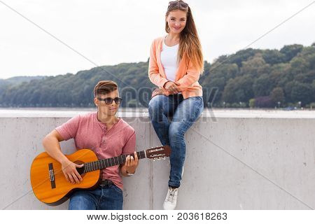 Romance dating sound talent valentines concept. Man expressing his love by music. Young girl listening to song played by boyfriend.