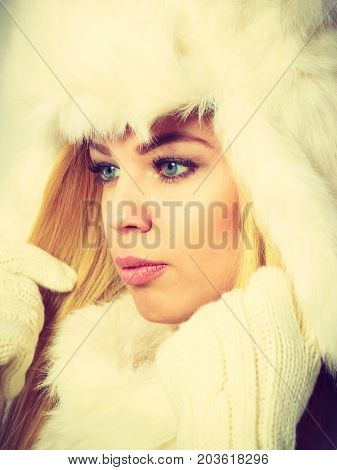 Winter fashion. Young blonde woman wearing fashionable wintertime clothes white fur scarf cap woolen gloves studio shot