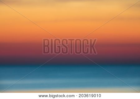 Intentionally blurred and defocused horizontal picture of clouds in the sky above calm sea surface during sunset