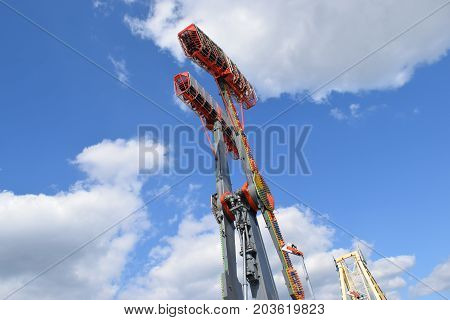 a thrill ride in the air against a blue cloudy sky.