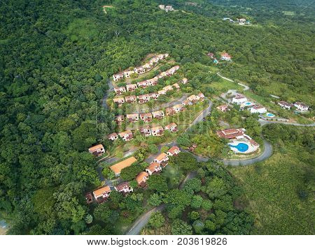 Houses on green hill aerial drone view. Eco village concept