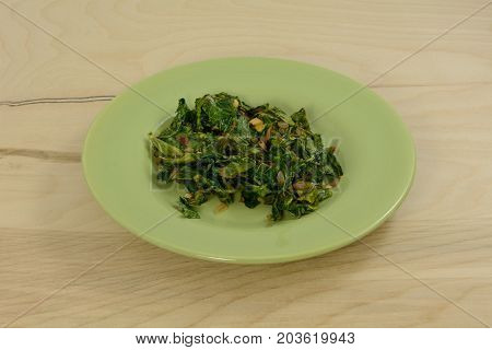 Cooked collard green salad on green plate