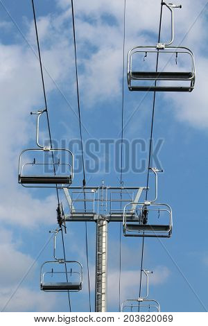 Overhead chair lift against a blue sky with clouds, vertical aspect