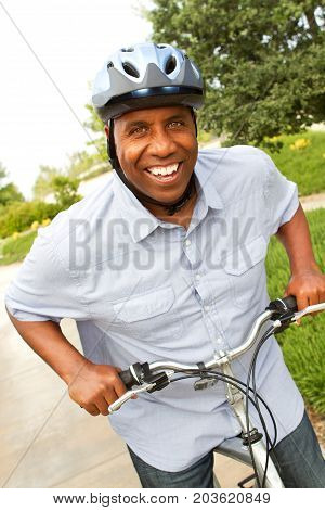 Mature African American man riding a bike.