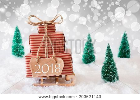 Sleigh Or Sled With Christmas Gifts Or Presents. Snowy Scenery With Snow And Trees. White Sparkling Background With Bokeh Effect. Label With Text 2018 For Happy New Year Greetings