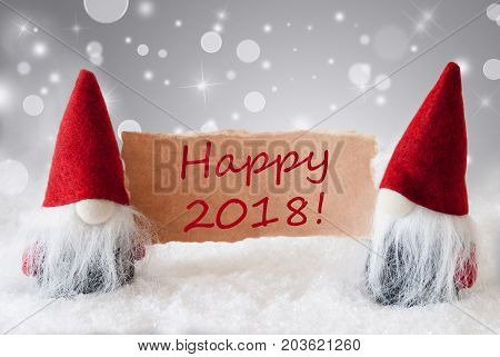 Christmas Greeting Card With Two Red Gnomes. Sparkling Bokeh And Noble Silver Background With Snow. English Text Happy 2018