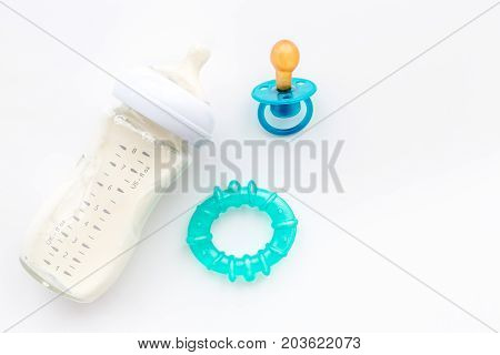 preparation of mixture baby feeding with infant formula powdered milk in bottle with toys on white desk background top view mock-up