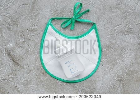 preparation of mixture baby feeding with infant formula powdered milk and bib on gray stone background top view