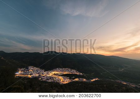 Long exposure of the religious town Moulay Idris in Morocco at sunset with a beautiful sky and some lightning in the streets.