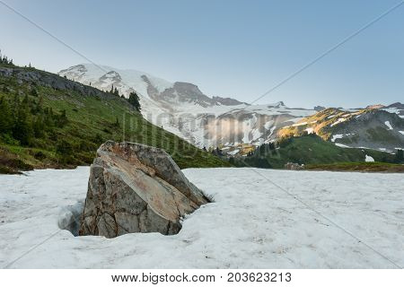 Rock Emerges From Snow In Alpine Meadow