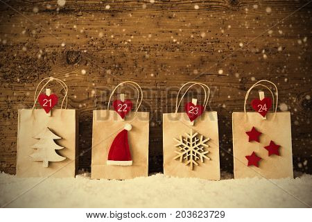 Christmas Shopping Bag With Numbers 21 to 24 In A Row. Decoration Like Santa Claus Hat, Snowflake, Christmas Tree And Stars. Wooden Background With Snow And Snowflakes And Instagram Filter