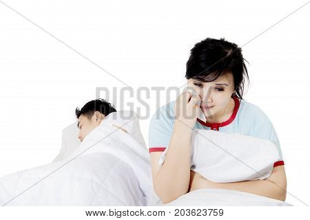 Image of young woman looks sad while suffering from insomnia and sitting with her asleep husband