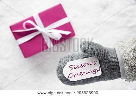 Glove With Label With English Text Seasons Greetings. Pink Gift Or Present On Snow In Background. Seasonal Greeting Card.