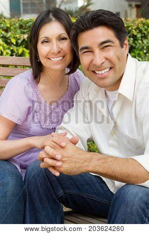 Happy Hispanic couple smiling outside in the backyard.
