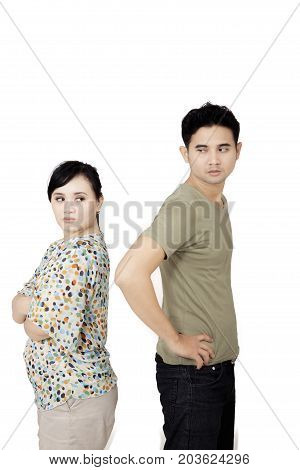 Portrait of young couple ignored at each other while having a quarrel isolated on white background