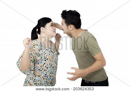 Young couple blaming each other while having quarreling isolated on white background