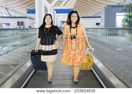 Image of two overweight women walking in the airport while carrying luggage