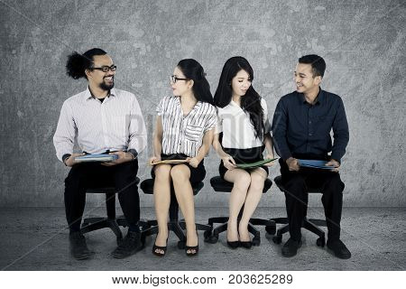 Group of young multiracial worker candidates chatting to each others while waiting for job interview