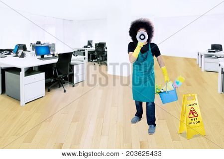 Young male janitor yelling with a megaphone while holding a bucket and standing near a wet floor sign in the office room