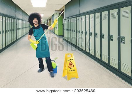 Happy male janitor playing guitar with a broom while standing with sign of wet floor in the hotel corridor
