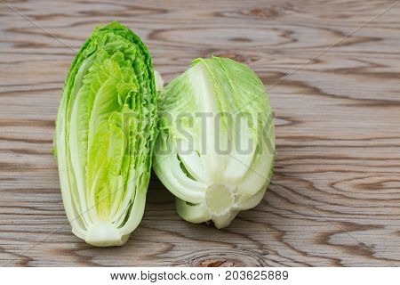 Fresh raw romaine lettuce on wooden table.