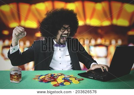 Cheerful young man with curly hair winning online poker with many chip and laptop on the table in casino