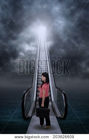 Asian businesswoman standing by the escalator on the sea