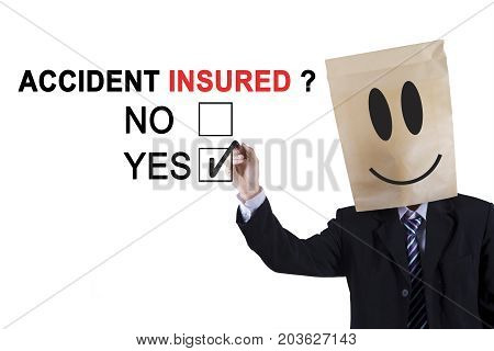 Anonymous businessman using a pen while selecting a yes option with a question of accident insured on the whiteboard