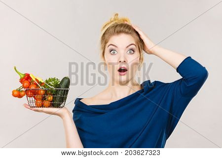 Adult woman do not like to eat raw food questioning healthy lifestyle recommendations origin vegetagles. Female holding small shopping basket with products displeased shocked face expression