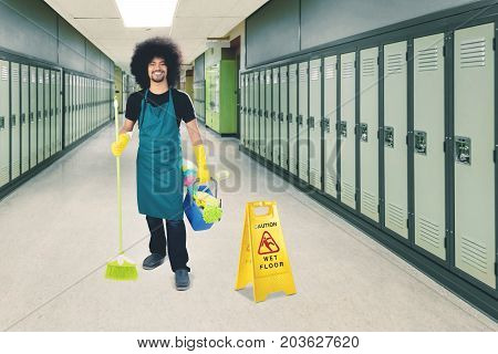 Image of male janitor holding a broom and bucket while standing with a wet floor sign in the school corridor