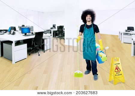 Picture of Afro male janitor carrying a broom and bucket while standing with a wet floor sign in the office
